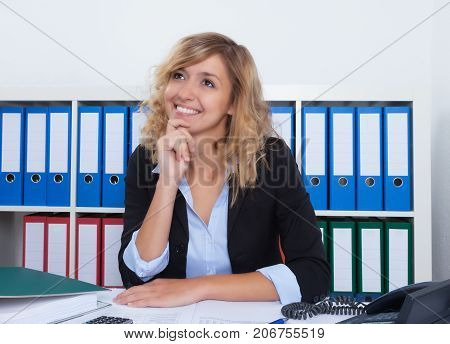 Dreaming businesswoman with curly blond hair at office