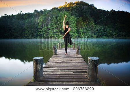 Yoga post on the wooded bridge in Pang ung park Pangung Mae Hong Son Thailand Asia