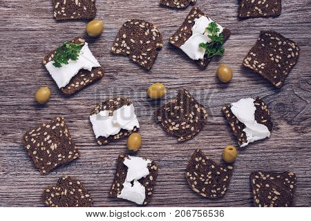 Rye croutons with cheese olives on a wooden background. Crackers with cheese top view