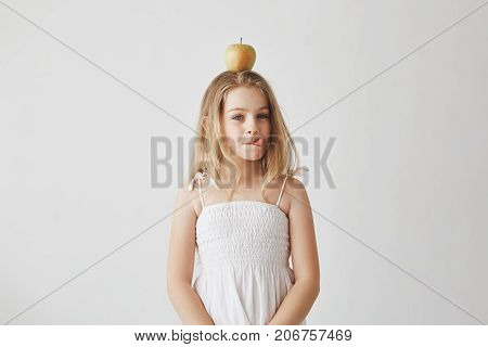 Portrait of funny cheerful girl with blond hair in white dress holding apple on head, showing tongue in camera, making silly expressions