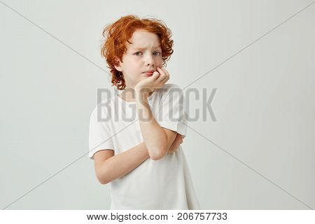 Portrait of cute little child with red hair and freckles holding head with hand thinking about homework he need to do till evening