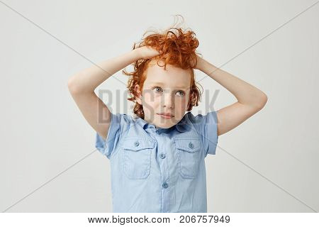 Portrait of joyful little ginger boy with wavy hair and freckles holding hair in hands, looking aside with tired and bored expression