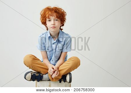 Portrait of bored little kid with red hair and freckles sitting on box with unhappy expression, being tired of waiting his mom wrom work