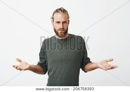 Handsome nordic man with beard and stylish hairdo spreads hands with cynical and mean expression when somebody pushed him on street