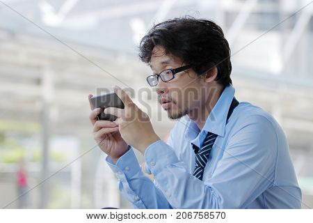 Close up of unemployed young Asian man looking mobile smart phone for find job. Unemployment concept.