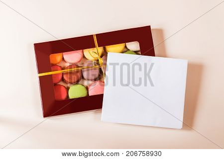 Note card and different colorful macaroons in gift box on beige background