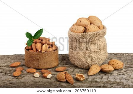 Almonds with leaf in bag from sacking on a wooden table with a white background.