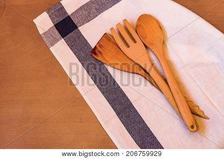 Wooden kitchen utensils and kitchen towel on wooden table