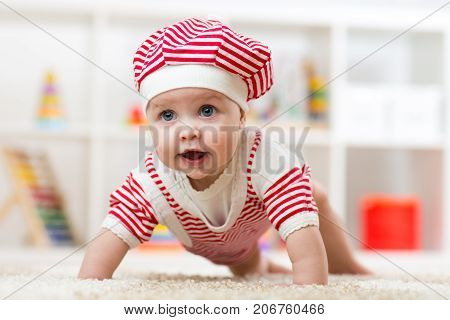 Six months old baby girl crawling on fluffy floor in nursery