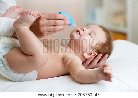 Mother or doctor cleans baby's nose with blower while infant tot is lying and smiling.