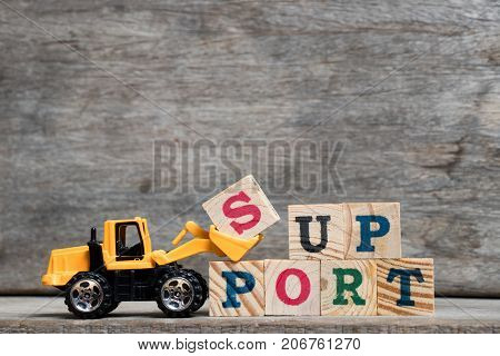Yellow plastic bulldozer hold letter S to complete word support on wood background