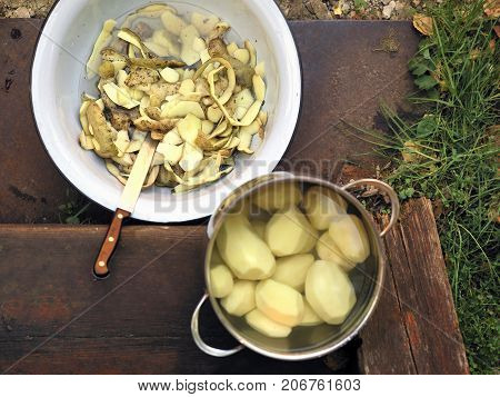 Peeled potato in a casserole and potato skin in a food bowl. Wooden steps in the background. Above view