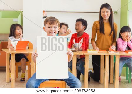 Cute boy holding blank white poster with happy face in kindergarten classroom kindergarten education concept Vintage effect style pictures.