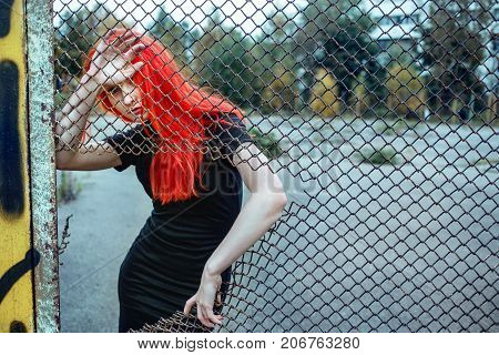 Fashionable redhead woman holding torn grid. Cold toning urban picture.