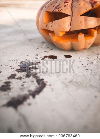 Halloween jack o lantern with red blood stains on ground. Pumpkin bleeding on cement background. Squash with carved smiley face. Autumn tradition and symbol. Holiday celebration concept