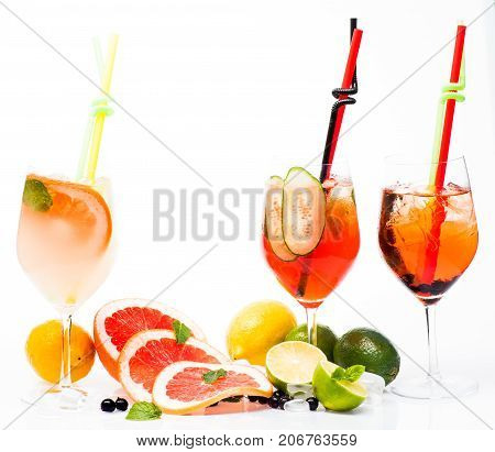 Fruit slice and cocktail glass at bar. Cocktails isolated on white. Alcoholic beverage and fruit at restaurant. Drink and food. Party and summer vacation.