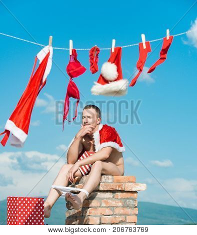 Christmas man with present box. New year guy with muscular body. Bad santa claus at clothes for drying on chimney. Laundry and dry cleaning. Xmas red costume on rope with pin.