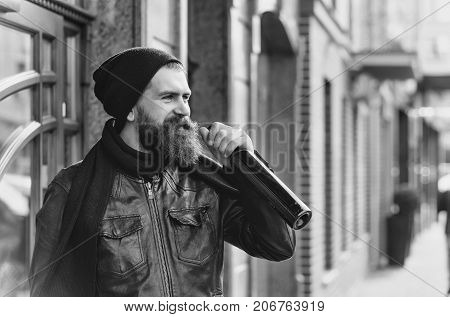 bearded man long beard brutal caucasian hipster with moustache holding glass wine bottle has smiling face in black leather jacket hat scarf unshaven guy with stylish hair near building outdoor