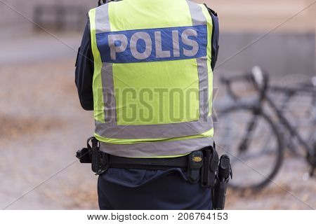 A Swedish Police Officer back with gun.