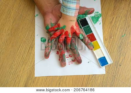 Hands in colorful paints and multicolor palette on white paper. Arts and handprint painting. Care love or adoption concept. Fathers day and family. Support and protection.