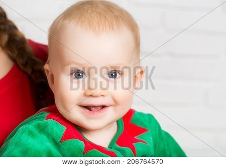 Christmas child with happy face. New year baby on hand of mother. Winter holiday and vacation. Xmas party celebration. Elf kid in costume of santa.