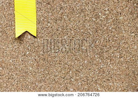 Closed up of brown cork board with yellow award ribbon background