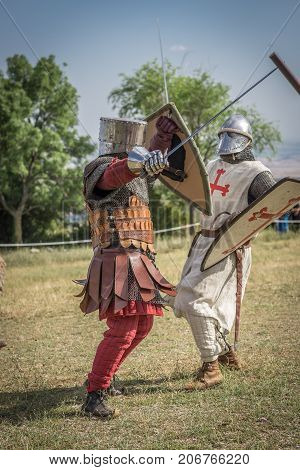 Medieval knight battle with swords and shields, reenactment with costumed characters and medieval armor with chainmail, helmet swords and shields. Medieval demonstration and recreation