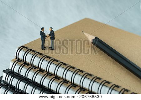 Miniature people: Small figure businessmen handshaking and standing on notebook with pencil as business agreement concept.