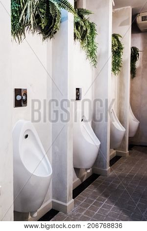 white urinal in men public toilet with black wall tile