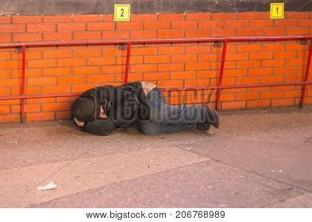 ZHYTOMYR UKRAINE - February 28 2016: The homeless man is sleeping on the street
