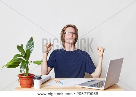 Successful Businessman At Work Place Clenches Fists, Celebrates His Victory And Triumph, Being Glad