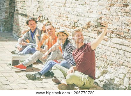 Group of multiracial friends taking a selfie with a mobile smartphone camera - Self portrait of happy persons sitting on the street and listening music with a vintage stereo - Focus on first man
