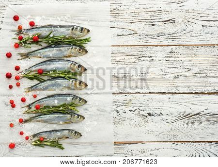 Fresh raw fish Baltic herring on white wooden table with fresh herbs and cowberry. View from above. Copyspace for text.