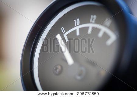 Close up shot of an analog car volt meter.