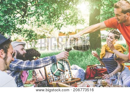 Group of friends having a picnic while eating and drinking wine in a park - Happy people having fun at backyard party on a sunny day - Friendship concept