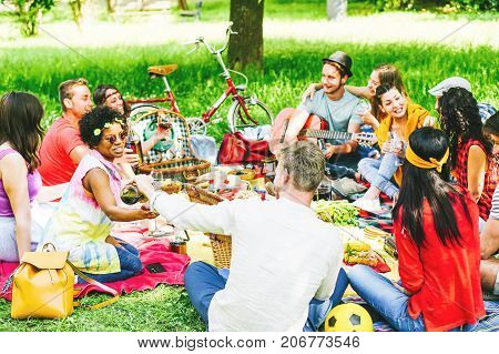 Group of friends enjoying a picnic while eating and drinking red wine sitting on blanket in a park outdoor - Young people having a funny meeting - Focus on left girl