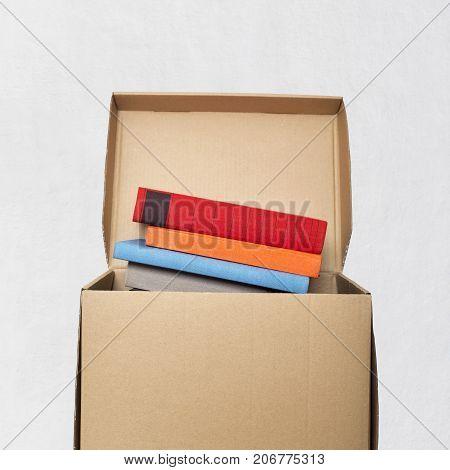 cardboard box full of books near the white wall