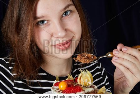 A girl with yogurt and strawberries in a cup