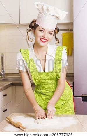 Young Woman Chef In Chef Hat Cooking Dough In Kitchen