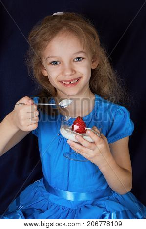A girl in a blue dress with yogurt and strawberries in a cup