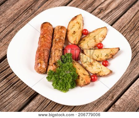 Delicious grilled wieners with fried potatoes and vegetables over a wooden background