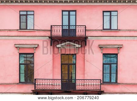 Several windows and balconies in a row on facade of urban apartment building front view St. Petersburg Russia