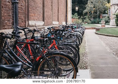 CAMBRIDGE, UK - SEPTEMBER 25, 2017: A row of bikes parked on the street in Cambridge. Cambridge has the highest level of cycling in the country with one in four residents cycling to work.