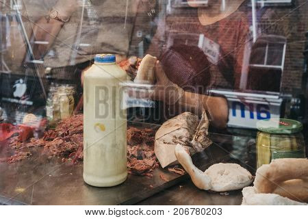 LONDON, UK - SEPTEMBER 24, 2017: Salt beef bagels being made a famous Beigel Shop in Brick Lane. The shop first opened in 1855 and sells fresh bagels 24 hours a day.