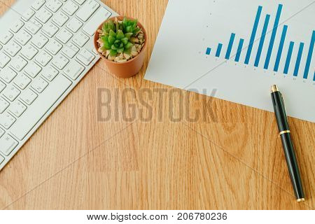Top View. Business Equipment Include Keyboard, Plant In Vase, Pen Placed On Info Graph Paper.  Woode