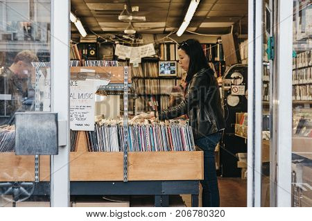 LONDON, UK - SEPTEMBER 24, 2017: Woman browse vinyl records at a store in Notting Hill, London. Vinyl experiences a renewed interest and increased sales in the past years.