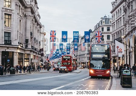 LONDON, UK - SEPTEMBER 24, 2017: Red double-decker buses on Regent Street, London. The street is decorated with NFL flags to celebrate the event and four NFL games played in capital in 2017.
