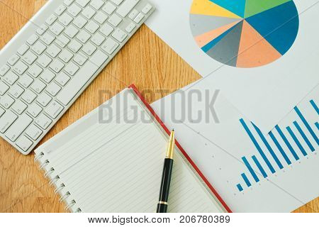 Top View. Pen Placed On Top Of Blank Notebook Paper With Keyboard, Bar Graph And Pie Chart Placed Ar