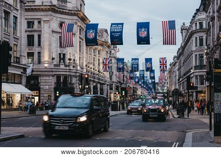 LONDON, UK - SEPTEMBER 24, 2017: Black taxi and cars on Regent Street, London. The street is decorated with NFL flags to celebrate the event and four NFL games played in capital in 2017.