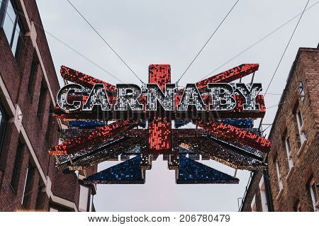 LONDON, UK - SEPTEMBER 24, 2017: Large Carnaby and Union Jack 3D shimmer sign over the junction between Carnaby Street and Ganton Street. It is made of 30,000 red, white and blue shimmer discs.